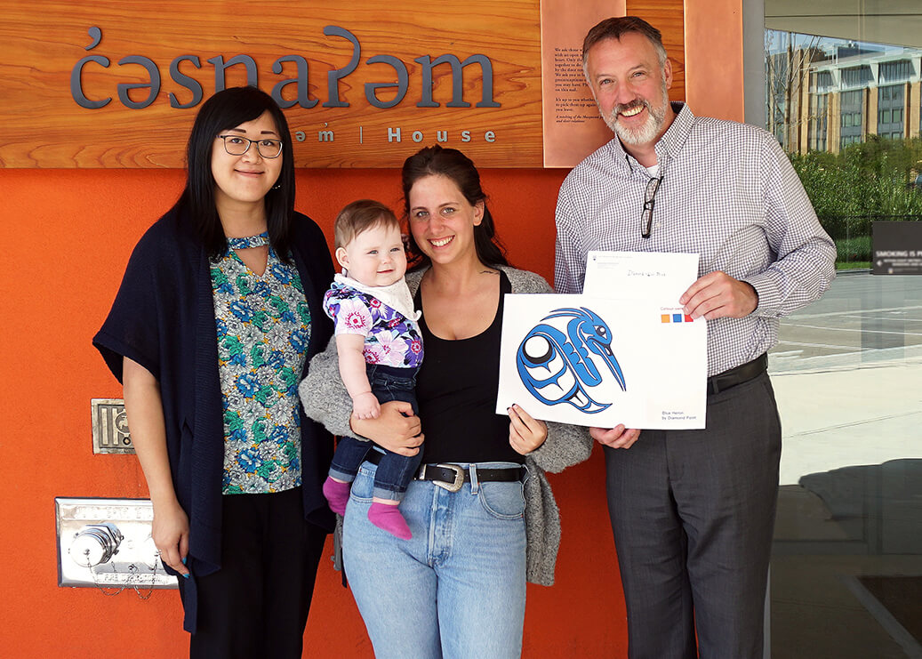 Sarah Ling, Project Manager-Indigenous Focus, SHHS (left) and Andrew Parr, Managing Director, SHHS (right), present Diamond Point and daughter Jade (centre) with the contest award at the entrance of Totem Park's c̓əsnaʔəm house.