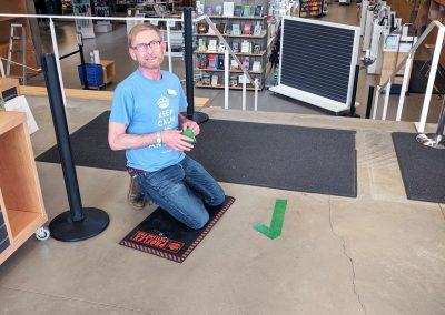 Ken placing directional markers on the floor of the UBC Bookstore.